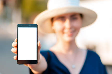 A woman in straw hat holds a smartphone in her hand, hand close-up. Portrait in a blur. Concept of modern technologies, business and applications for the phone.