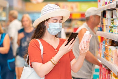 Portrait of young woman in a medical mask scans the qr code on the product using her smartphone. In the background is a supermarket. The concept of modern technology and shopping during the pandemic. Imagens