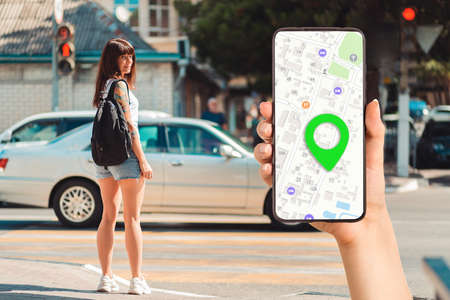 A hand holds a smartphone with an online map app and a marked destination. In the background, a woman stands at a pedestrian crossing. The concept of online navigation and modern technologies.