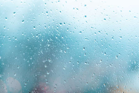 Raindrops on the window, the background is blurred. Gray color. Copy space. Banco de Imagens