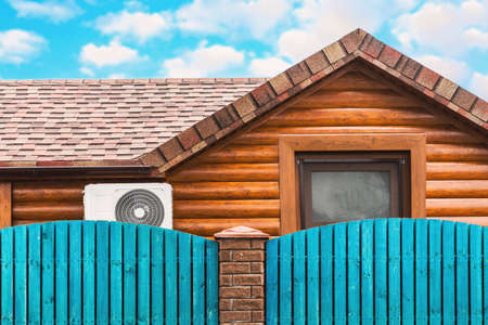 Wooden house with air conditioning, surrounded by a blue fence. Blue sky with clouds. Bright colors.