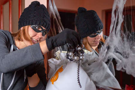 A female robber in a mask, with a stolen bag of money in her hands, examines the stolen jewelry. Reflection in the mirror, with cobwebs on the frame. The concept of theft and crime.