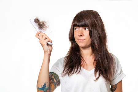 A woman with tattoos, holding a comb with a tuft of torn hair. White background. The concept of loss of hair.