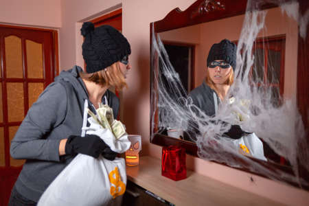 A woman in a robber's costume, holding a bag of money and looking scared in the reflection in the mirror, with a web on the frame. The concept of Halloween and holiday. Stok Fotoğraf