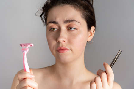 A young pretty woman holding a pair of tweezers and a razor, not knowing how to remove excess hair on her face. The concept of getting rid of unwanted hair. Archivio Fotografico