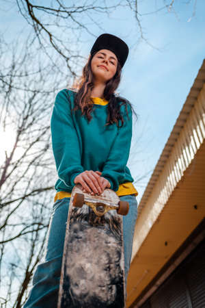 Portrait of A young pretty Caucasian woman leaning her hands on a skateboard. In the background, the blue sky and tree branches. Vertical. Bottom view. Concept of sports lifestyle and street culture. Stock fotó