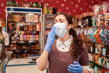 Virus. A woman in rubber gloves and a medical mask covers her mouth to sneeze. Grocery store, small business. Concept of protection against coronavirus and security measures.