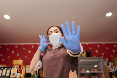 Virus. A woman in rubber gloves and a medical mask, in horror, defends her hands. Bottom view. Grocery store, small business crisis. Concept of protection against coronavirus and security measures.