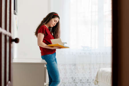A young woman stands and flips through a book, the view from behind the door. White interior of the room in the background. Education concept and world book day.