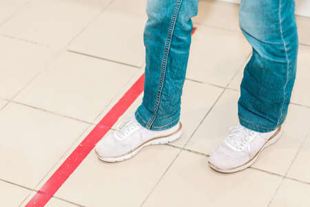 Person stand in red line, legs close-up. Attention line on the floor of the store to maintain social distance. Concept of the coronavirus pandemic and prevention measures. Stock fotó