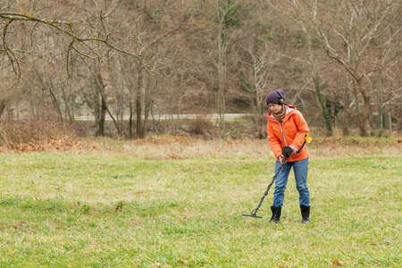 a girl in an orange jacket with a metal detector in his hands, is on the field in search of antiquity. Banque d'images