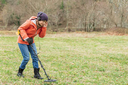 young woman enthusiastically explores the soil with a detector.