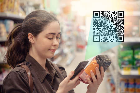 Young lovely woman scans the product in the supermarket. The concept of modern technology. Light.