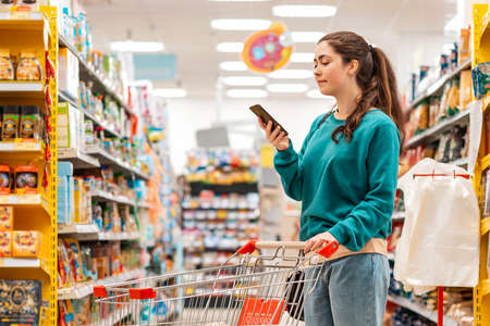 A young pretty Caucasian woman in casual clothes, pushing a grocery cart and using a mobile phone. Copy space. The concept of shopping and buying food and communication.