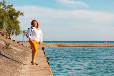 The summer and holidays. A happy overweight woman poses on a sea pier. Copy space.