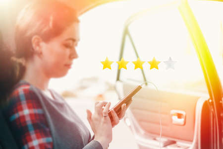 The concept of mobile applications on the taxi. A young woman gets into the car and writes a review in the application about the taxi. In the background is an open door. Stars rating at first plan. Stock Photo