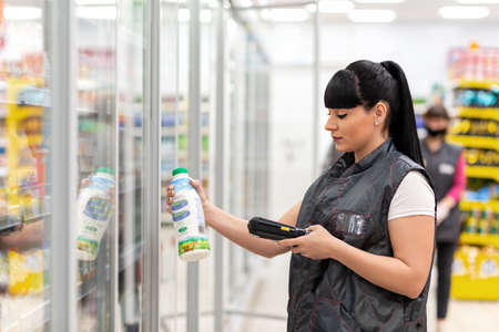 A young Caucasian woman who works as a Manager in a supermarket checks the expiration date of the product through an electronic device. Side view. Business and technology concepts. 版權商用圖片