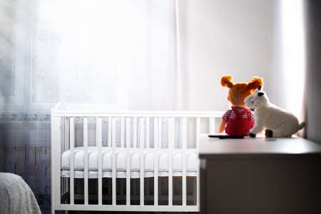 Children's room with an empty cradle and toys on the dresser. Copy space. The concept of abortion and female infertility.