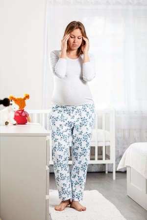 A young pregnant woman suffers from a headache and holds her hands over her temples. Children's room in the background. The concept of the health of pregnant women, motherhood. Vertical.