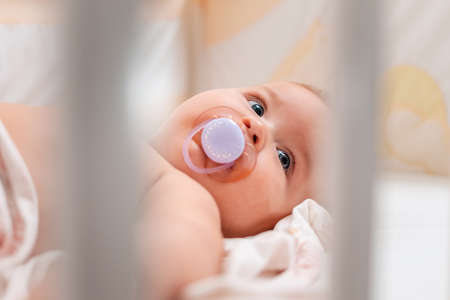 Close up portrait of a baby with a pacifier in his mouth, who is lying in a cradle. View through the bars of the cradle. Standard-Bild