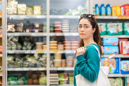 A young pretty Caucasian woman with an eco-bag on her shoulder, posing against the background of refrigerators with food. The concept of purchasing goods and shopping.