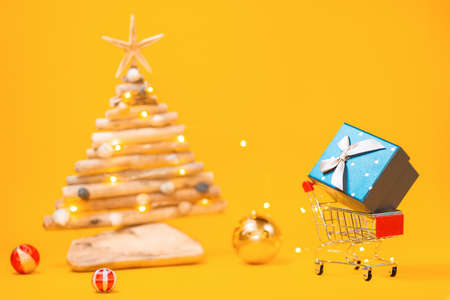 Holiday shopping. A toy shopping cart with a gift, and a blurred craft wooden Christmas tree with christmas ball. Yellow background. Copy space. Concept of Christmas sales.