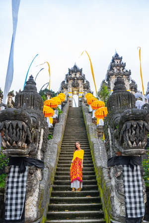 Bottom-up view of the Balinese temple decorated for the holiday Galungan. Woman standind on the stairs. Bali, Indonesia.