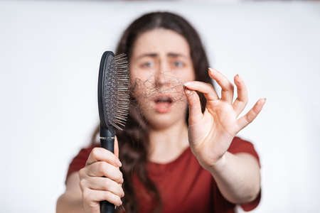 Portrait in a blur, a screaming brunette woman holds a comb in front of her, clearing it from a pile of fallen hair. White background. Concept of hair loss, baldness and hair care.
