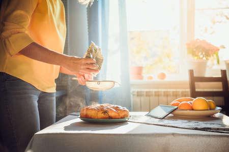 Women bake fragnant pie and sprinkle the homemade pie with powdered sugar. Reklamní fotografie