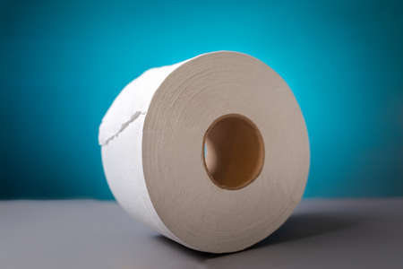 A roll of toilet paper on blue background close-up. The concept of panic purchasing of essential goods. Coronovirus, pandemic, hygiene.