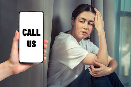 Portrait of stressed woman clutching her head with her hand. Hand with a smartphone with a call the support hotline. The concept of domestic violence.