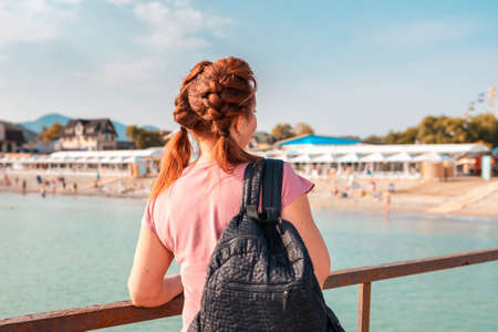 An adult woman with a backpack admires the ocean and the beach. View from the back. Close up. The concept of freedom and travel.