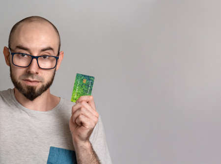 The concept of banking and credit card purchases. A man in glasses smiles and holds a Bank card in his hands. Close up and copy space.