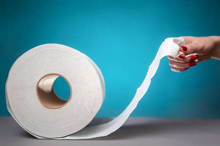 Hand holding the edge of a roll of toilet paper, on a blue background close-up. The concept of panic purchasing of essential goods. Coronovirus, pandemic, hygiene.