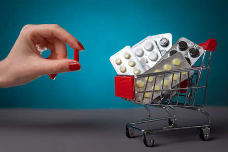 A woman with a red manicure puts a red pill in a small cart filled with pills. Turquoise background. Copy space. Concept of pharmaceuticals, coronovirus and business. Zdjęcie Seryjne