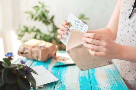 A woman takes a postcard out of a craft envelope. Hands close-up. Blue wooden table with a parcel in the background. Concept of postcrossing.