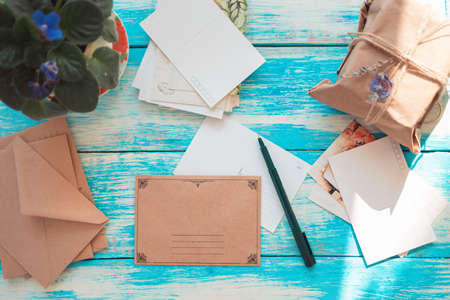 Vintage composition of postcards, pen, envelopes, and parcel. Blue wooden background. Flat lay. Copy space. The concept of mail and postcrossing.