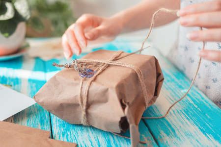 A female hands unpacks a parcel packed in craft paper with dried flowers. Close-up. Concept of receiving parcels and unboxing.