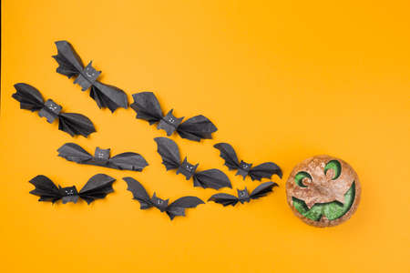 A flock of bats made of paper flies to the pumpkin with the image of a face. Orange background. Flat lay. Copy space. The concept of Halloween, and holiday decorations. Stock fotó
