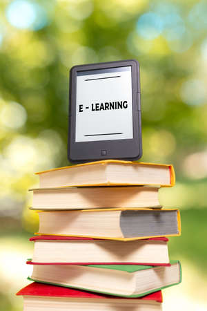 E-learning and reading. E-book reader is at the top of the stack of books. The Park is blurred in the background. Concept of education and electronic gadgets.