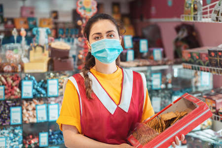 Female worker in uniform with a medical mask on her face, holding a box of goods. Showcase with products in the background. The concept of measures of protection in the stores during coronavirus.