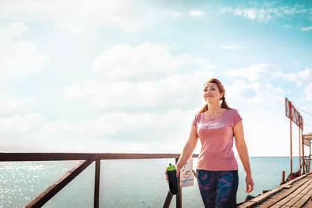 Sea and freedom. Adult woman in sportswear with a shaker in her hands, walking along the pier pier. Copy space. Outdoor walk.