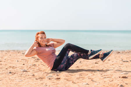 Adult happy woman in sportswear, swinging abs, sitting on the sand. Sea in the background. Copy space. Training outdoor.