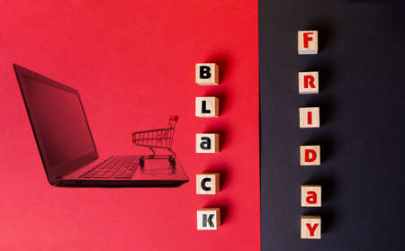 Discounts and sales. On a red and black background are wooden cubes with the inscription black Friday. Flat lay. Image of a laptop with a shopping cart on the red half of the background.