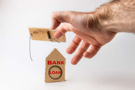 Bank investments and risks. A man's hand caught in a mousetrap, there is a cardboard schematic house with the inscription BANK LOAN. Banco de Imagens