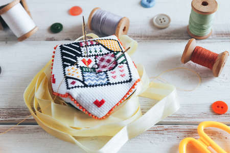 Handmade and needlework. Handmade pin cushion with a simple ornament and sewing supplies on the white background. Top view.
