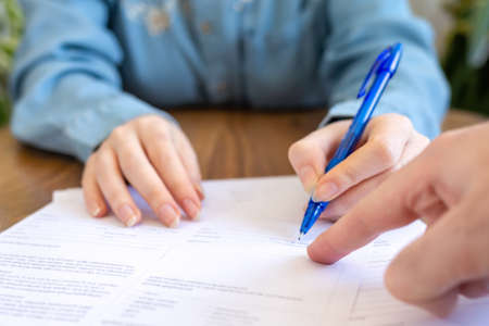 World leasing day. The employee points his finger at the contract where you need to sign it. Hands close-up. Rental and purchase of real estate.