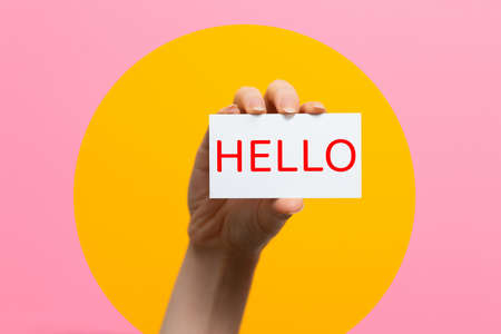 World hello day. Raised female hand with a card with the inscription Hello. Pink background with a yellow circle.
