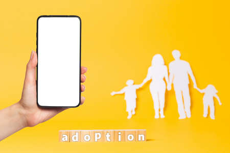 A family cut out of white paper on a yellow background. Wooden cubes with the inscription adoption. On the left, a woman's hand holds a smartphone. Mock up. The concept of adoption. 版權商用圖片