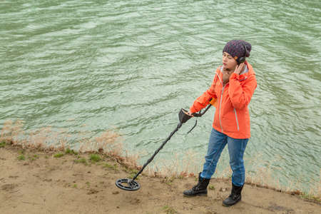 girl with a metal detector explores the ground near the river.